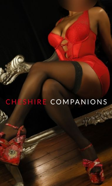 Amber sat on a black couch wearing a tight red dress, stockings and red heels