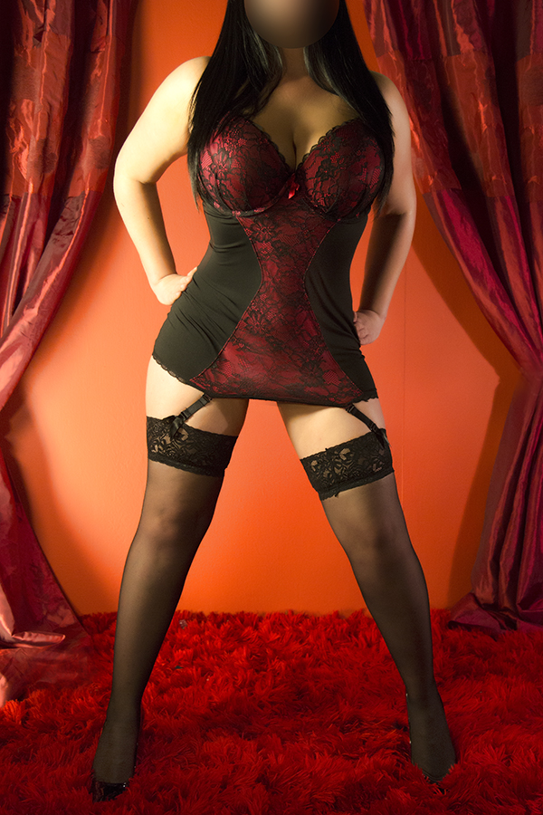 Millie from the front wearing her red and black lace body suit with suspenders and high heels